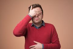Man in red sweater covering eyes trying to stay away from problems. stock photos