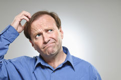 Mature Caucasian Man Scratching Head. A mature man in his 50's scratching his head while making a decision royalty free stock image