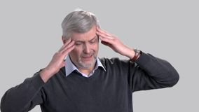 Mature caucasian man suffering from headache. Stressed man rubbing his temples because of strong headache on grey background. Portrait of overworked man with stock video