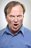Mature Caucasian Man Yelling Angrily. A mature man in his 50's furiously yelling with anger Royalty Free Stock Photo