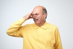 Mature caucasian man in yellow tshirtwith disgust on his face pinches nose. Something stinks, very bad smell. Negative emotion facial expression Royalty Free Stock Photos