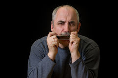 Mature Caucasian moustached man playing mouth organ Royalty Free Stock Image