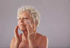Mature caucasian woman applying anti-wrinkle face cream. Royalty Free Stock Photo
