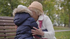 Mature Caucasian woman in beige cloche hat and white coat sitting on the bench with her granddaughter. Happy grandmother. Talking to a young lady in the autumn stock video