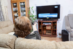 Mature Caucasian woman pushing tv remote control Royalty Free Stock Photo