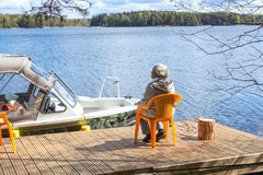 Mature Caucasian woman relaxing at lake sitting on pier Royalty Free Stock Photography