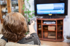 Mature Caucasian woman turning tv channels with remote control royalty free stock image