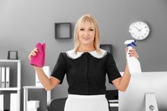 Mature charwoman with bottle of detergent and rag. For cleaning office royalty free stock image