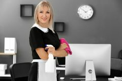 Mature charwoman with bottle of detergent. And rag for cleaning office stock photo