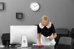 Mature charwoman cleaning office. Mature charwoman cleaning the office royalty free stock photography