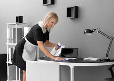 Mature charwoman cleaning office. Mature charwoman cleaning the office stock image