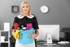 Mature charwoman with cleaning supplies. In office royalty free stock photos