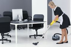 Mature charwoman hoovering floor in office. With vacuum cleaner royalty free stock photography