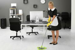 Mature charwoman mopping floor. In office Stock Image