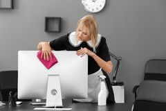 Mature charwoman wiping dust from PC monitor. In office stock photo