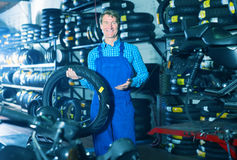 Mature cheerful mechanic holding new tyre for motorcycle. In workshop Royalty Free Stock Image