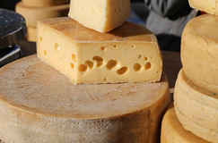 Mature cheese with holes for sale in the market Royalty Free Stock Photo