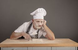 Mature chef covered in flour looking annoyed and fed up stock photo