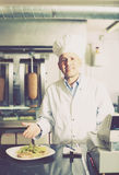 Mature chef in fast food restaurant Royalty Free Stock Images