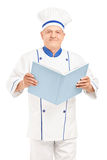 A mature chef holding a cookbook and looking at camera Stock Images