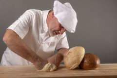 Mature Chef kneading bread dough. In a kitchen setting royalty free stock photo