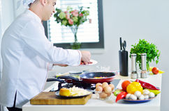 Mature chef preparing a meal with various vegetables and meat Stock Photo
