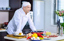 Mature chef preparing a meal with various vegetables and meat Stock Photos