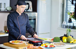 Mature chef preparing a meal with various vegetables and meat Royalty Free Stock Photo