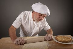 Mature chef rolling out pastry dough. In a kitchen setting royalty free stock image