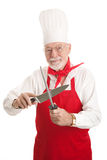 Mature Chef Sharpens Knife. Handsome experienced chef sharpening his knife.  Isolated on white Royalty Free Stock Photography