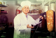 Mature chef slicing kebab in fast food Royalty Free Stock Image