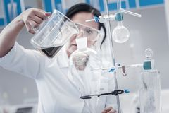 Mature chemist pouring liquid into separating funnel. Careful process. Selective focus on a lab glassware fixed on a metal stand and a hand of a female Stock Photos