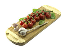 Mature Cherry tomatoes on a cutting board on a white background. Royalty Free Stock Images
