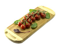 Mature Cherry tomatoes on a cutting board on a white background. Royalty Free Stock Photos