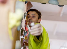 Mature Climber getting the hold on climbing wall Stock Photography