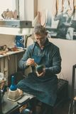 mature cobbler holding boot workpiece and working with sole while sitting at at his stock photo