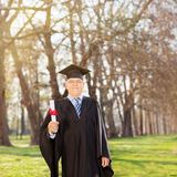 Mature college graduate holding a diploma in park Stock Photo