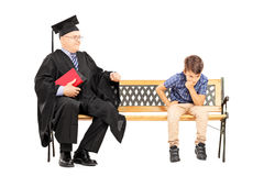 Mature college professor and a thoughtful kid seated on bench. Isolated on white background royalty free stock photos