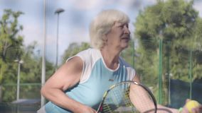 Mature concentrated woman holding a racket and ball about to pass on the tennis court. Active leisure outdoors. Shooting. Mature concentrated woman holding stock video