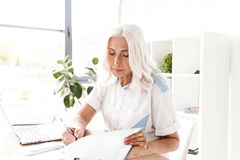 Mature concentrated woman writing notes. stock photos