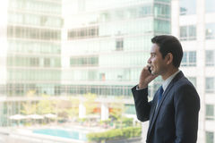 Mature and confident business executive looking looking out of large windows at a view of the city below. Stock Photography