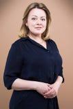 Mature confident woman. Studio shot on brown background Stock Photos