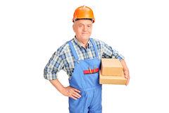 Mature construction worker holding boxes Royalty Free Stock Images