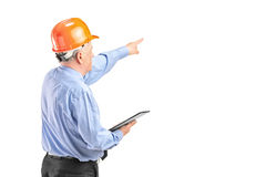 Mature construction worker holding a clipboard. A mature construction worker with helmet holding a clipboard and pointing isolated on white background Stock Image