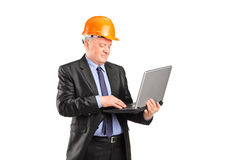 Mature construction worker working on a laptop Royalty Free Stock Photography