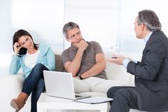 Mature consultant explaining to couple Stock Image