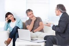 Mature consultant explaining to couple. Mature Consultant Trying To Explain Worried Couple Stock Image