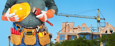 Mature contractor and hoisting crane Royalty Free Stock Photography