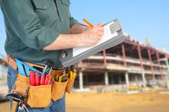 Mature contractor and instruments. Mature contractor working. Worker writes in a business notebook Stock Photography