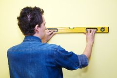 Contractor plasterer. Mature contractor plasterer working indoors in yellow room Royalty Free Stock Images